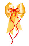 Golden bow with red ribbon made from silk Royalty Free Stock Images