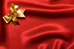 Golden bow on a red silk. Royalty Free Stock Photo