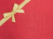 Golden bow on red silk Stock Photography