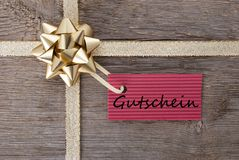 Golden bow with red tag with Gutschein Royalty Free Stock Images