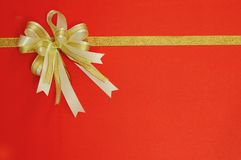 Golden Bow and ribbon on red Royalty Free Stock Photos
