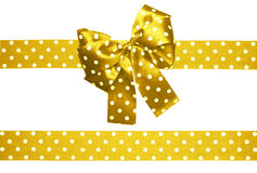 Golden bow and ribbon with white polka dots made from silk Stock Photos