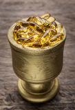 Golden Bowl with golden diet pills. Vitamin E. Royalty Free Stock Images