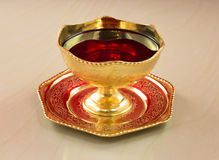 Golden bowl with red wine on a marble table Stock Photography