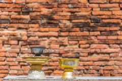 Golden bowl with ritual offerings against brick wall on the back. Ground. Buddhism ceremony Royalty Free Stock Photo