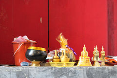 Golden bowls and statuettes of Buddha were placed on the edge of a window in a temple (Thailand) Royalty Free Stock Photography
