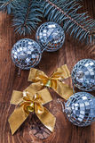 Golden Bows And Christmas Disco Balls With Pinetree Branch On Old Wooden Board Royalty Free Stock Images