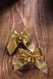 Golden bows with small bells on old wooden board Stock Images