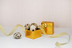 Golden box with Easter eggs and ribbon Royalty Free Stock Image