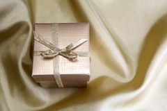 Golden box with ribbon on golden silk Royalty Free Stock Photography