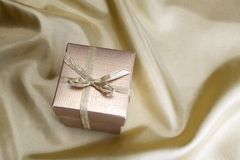Golden box with ribbon on golden silk Royalty Free Stock Image