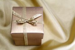Golden box with ribbon on golden silk Stock Photo