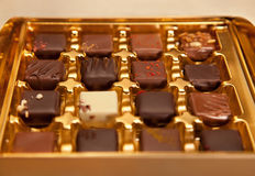 Golden Box of Square Shaped Chocolates in Different Colors and Types Stock Photo