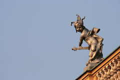 Golden boy. Baroque sculpture as decoration on the top of the roof Stock Photo