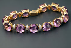 Golden bracelet with amethysts. Golden jewelry  bracelet with amethysts  and brilliants on grey  background Royalty Free Stock Images