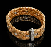 Golden bracelet with diamonds. Over black background Stock Photos