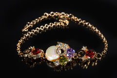 Golden bracelet with precious stones on black Stock Images