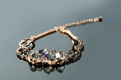 Golden bracelet with precious stones on grey Stock Photos