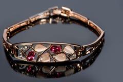 Golden bracelet with precious stones on grey Stock Photography