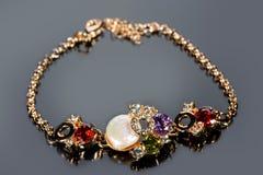 Golden bracelet with precious stones on grey Stock Photos
