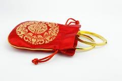 Golden bracelets and red bag Stock Image