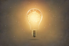 Golden brain glowing inside light bulb on paper texture backgrond. Golden brain glowing inside of light bulb on paper texture background Royalty Free Stock Photos