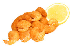 Golden Breadcrumb Coated Prawns. Golden breadcrumb coated cooked prawns with lemon isolated on a white background Royalty Free Stock Photo
