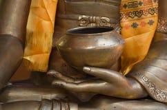 Golden bronze buddha hand holding a singing bowl. Royalty Free Stock Photos