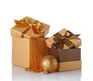 Golden and brown classic gift boxes with satin bows, beaded garlands and glass christmas ball. Isolated on white background Royalty Free Stock Photos