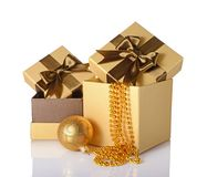 Golden and brown classic gift boxes with satin bows, beaded garlands and glass christmas ball. Isolated on white background Stock Photo