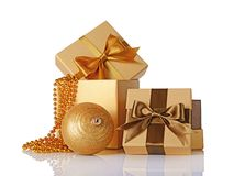 Golden and brown classic gift boxes with satin bows, beaded garlands and glass christmas ball. Isolated on white background Stock Images