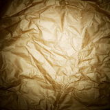 Golden brown crisped paped background. With spotlight in the center and dark edges stock images
