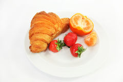 Golden brown croissant and fruits on plate