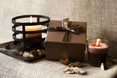 Golden-brown gift box with candles on wooden plate. Burlap/sack. Backround Stock Images