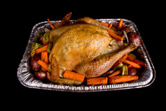 Golden brown Holiday Turkey. Golden brown Holiday Dinner Turkey in a roasting pan with orange carrots, green celery and red potatoes Stock Photography