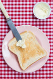 A golden brown slice of toast on a pink plate with butter Stock Images