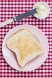 A golden brown slice of toast on a pink plate with butter Stock Image