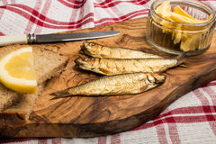 Golden brown smoked sprats on wooden board Royalty Free Stock Images
