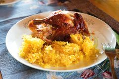 Baked chicken with saffron rice, closeup. Golden browned baked chicken with saffron rice , closeup on white plate Stock Images