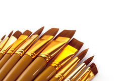 Golden brushes. Set of new artist paintbrushes with striking gold ferrules. Room for text and image extension Stock Photos