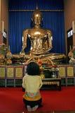 Golden Budda. Solid gold Budda statue and a praying woman in Wat Traimit temple, Bangkok, Thailand Royalty Free Stock Photos