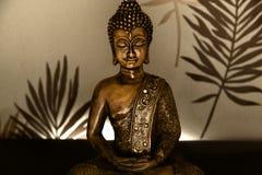 Golden Buddha. Buddha in lotus position with Illumine background Stock Photos