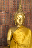 Golden Buddha against red bricks Stock Images