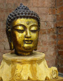 Golden Buddha. Antique golden Buddha on the brick wall background Royalty Free Stock Images