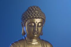 Golden Buddha is on the blue background Royalty Free Stock Images