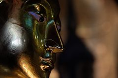 Golden Buddha face. Closeup on a Buddha statue Royalty Free Stock Photos