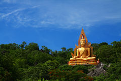 Golden buddha on green mountain. Big golden buddha on green mountain with clear sky,Rachaburi Thailand Royalty Free Stock Image