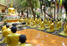 Golden Buddha and monks statues in Buddhist temple Stock Image