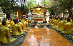 Golden Buddha and monks statues in Buddhist temple Royalty Free Stock Photos
