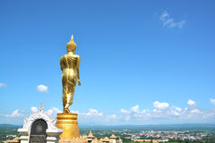 Golden buddha on mountain with blue sky at Wat Phra That Kao Noi Royalty Free Stock Photos